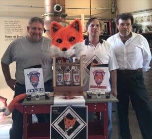Three owners of Hunt Club Distillery standing by display